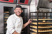 Smiling Baker putting a rack of pastries into the oven in bakery or pastry shop .