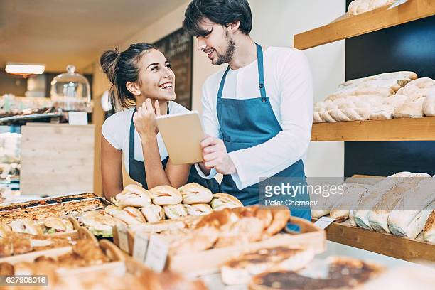 Smiling bakers with digital tablet