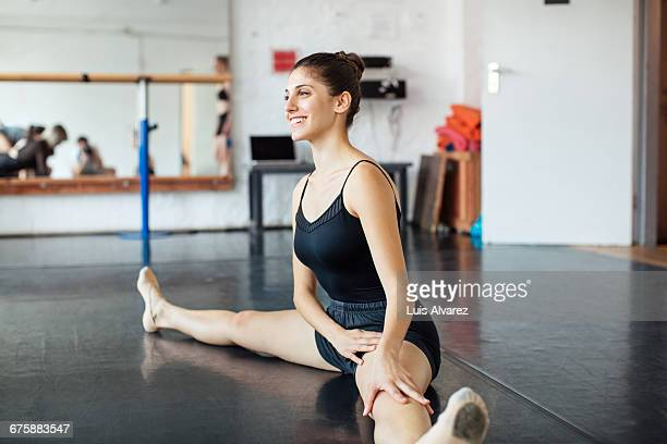 Smiling ballet dancer sitting in splits at studio