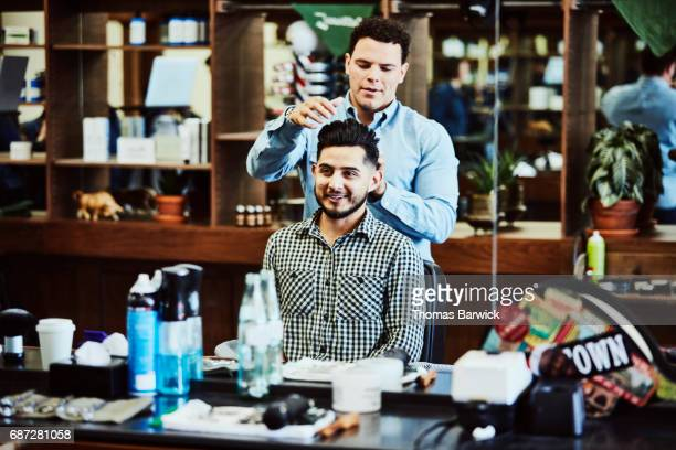 Smiling barber and client admiring hair cut in mirror in barber shop