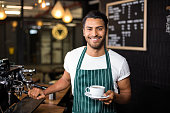 Smiling barista making coffee with coffee machine in the bar