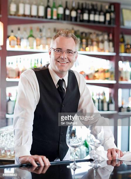 Smiling bartender behind bar.