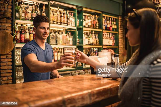 Smiling bartender giving beer to a young woman in bar.