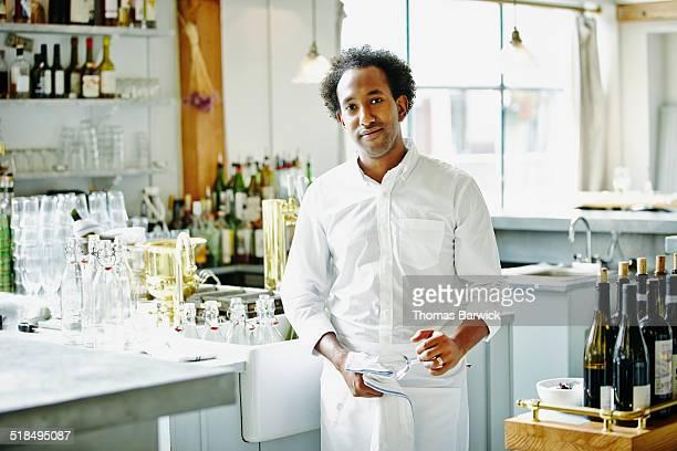 Smiling bartender standing in restaurant bar