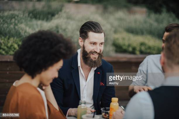 Smiling bearded businessman sitting with colleagues