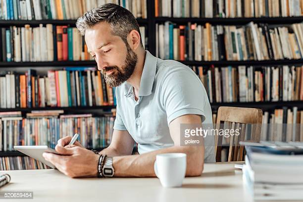 smiling bearded creative drawing on tablet in home office