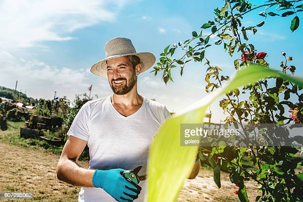 smiling bearded farmer man with sun hat working on farm