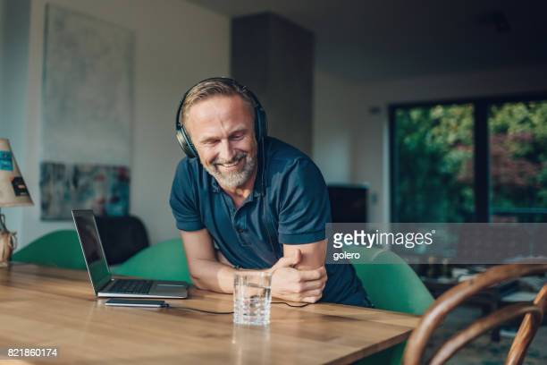 smiling bearded midaged man with headphones and laptop at table
