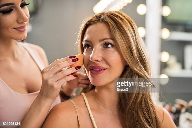 Smiling beautician applying face powder on beautiful woman.