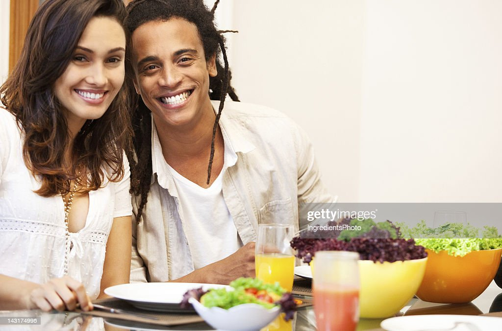Smiling beautiful brazilian couple having lunch at home with friends. : Stock Photo
