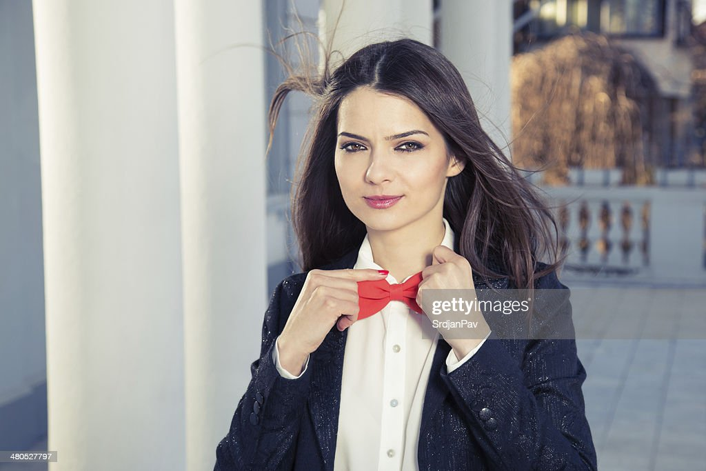 Smiling beautiful girl with bow tie, wind in the hair : Stock Photo
