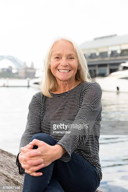 Smiling beautiful happy blond mature woman sitting near water