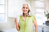 Portrait of a smiling, beautiful senior lady drinking a glass of milk