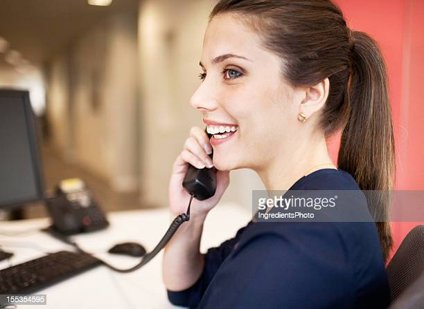Smiling beautiful woman at her workplace talking on the phone.