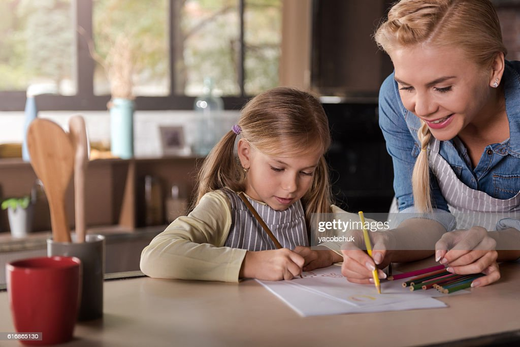 Smiling beautiful woman drawing with her daughter in the kitchen : Stock Photo