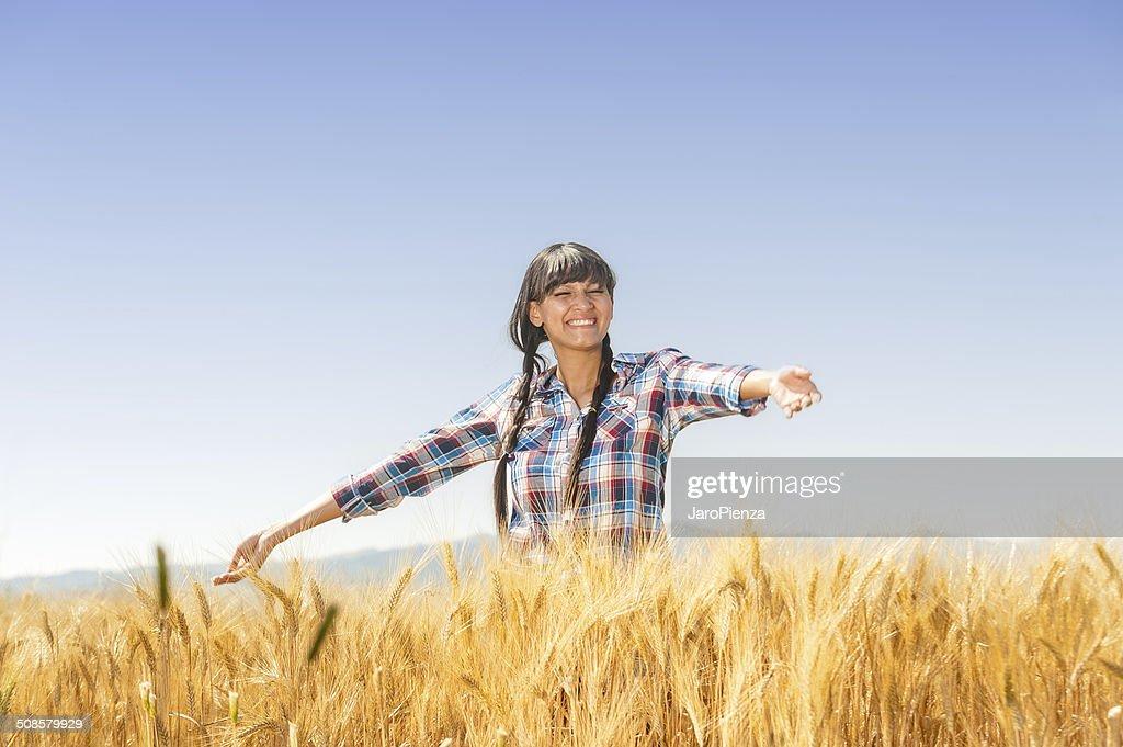 Smiling beautiful young brazilian girl on a yellow crop field : Stock Photo