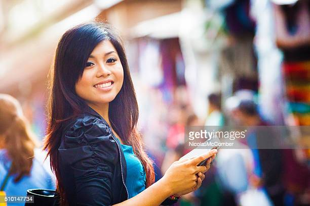 Smiling beautiful young Indonesian woman portrait with phone