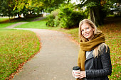 Smiling beautiful woman in park with coffee