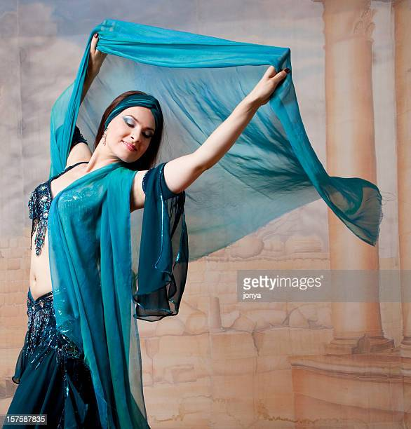 smiling belly dancer throwing veil in the air