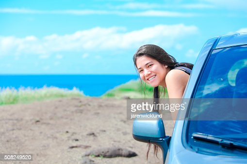 Smiling biracial teen girl leaning out car door by ocean : Stock Photo