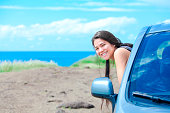 Smiling biracial teen girl leaning out car window on sunny day at  beach with blue Hawaiian ocean in background