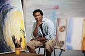 Smiling Black Artist sitting in studio