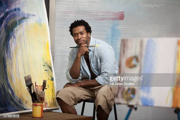 Smiling Black Artist sitting in studio