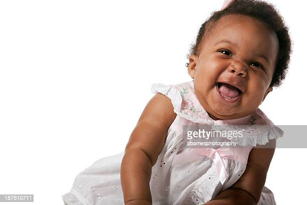 smiling black baby wearing lacy pink gown sitting on floor