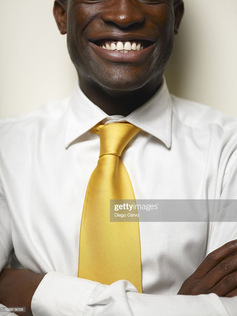 Smiling Black businessman with arms crossed : Stock Photo