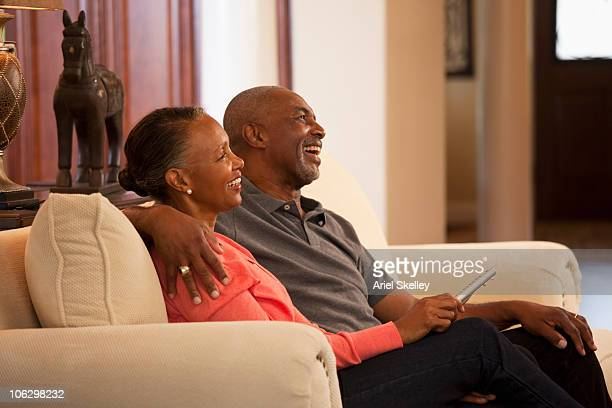 Smiling Black couple watching TV on living room sofa