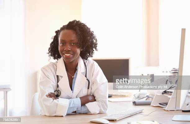 Smiling Black doctor at computer desk