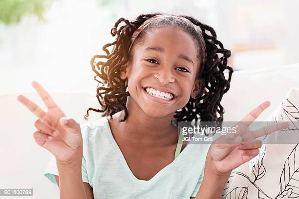 Smiling Black girl making peace sign