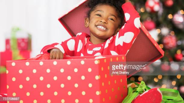 Smiling Black girl opening red gift box on Christmas