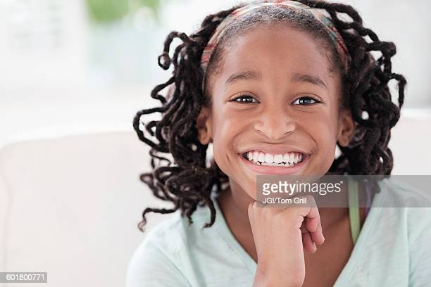 Smiling Black girl resting chin in hand