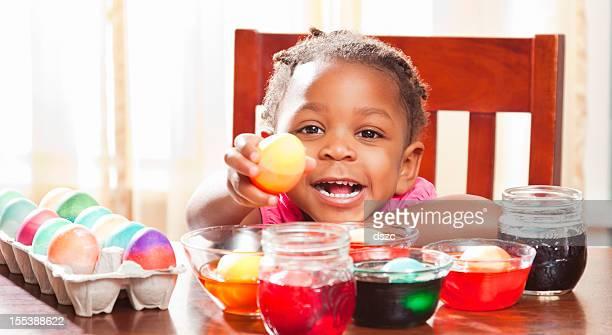 Lächelnd Schwarz kleines Mädchen Färbung Eier für Ostern Kind