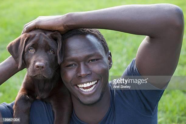 Smiling Black man holding puppy