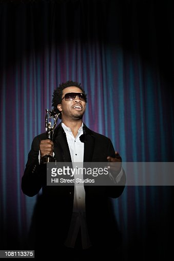 Smiling Black man in tuxedo holding award trophy : Stock Photo