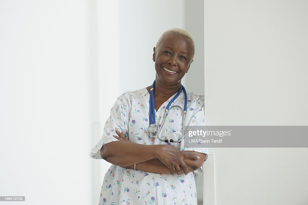 Smiling Black nurse leaning on wall : Stock Photo