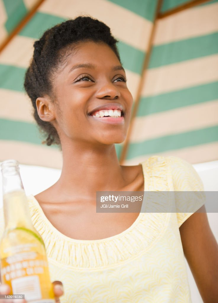 Smiling Black woman drinking beer : Stock Photo