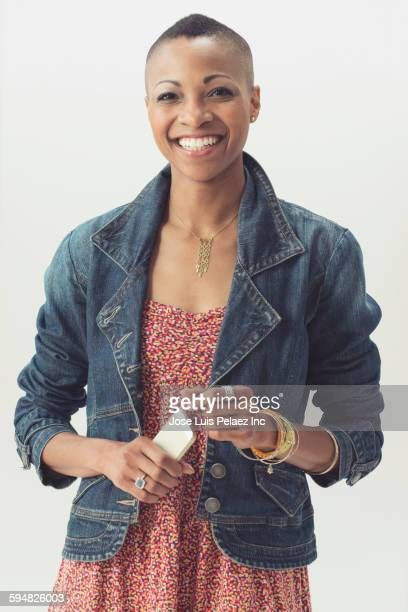 Smiling Black woman holding cell phone