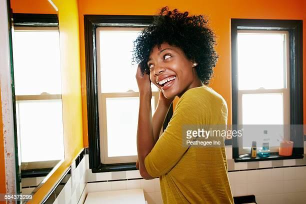 Smiling black woman styling hair in bathroom mirror
