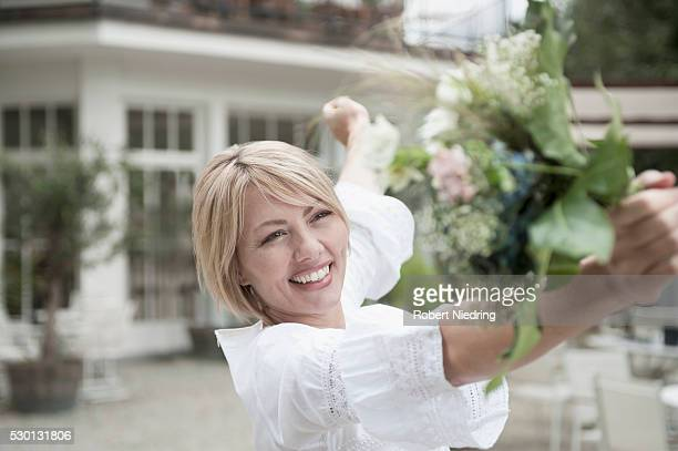 Smiling blond woman holding wedding bouquet
