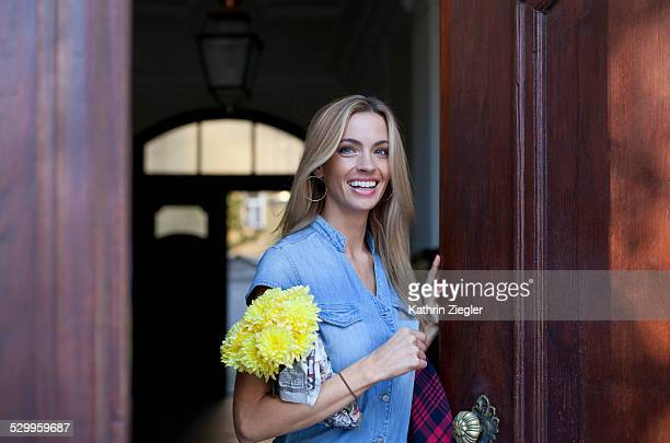 smiling blond woman stepping out of door