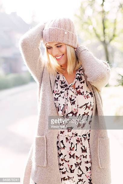 Smiling blond woman wearing patterned dress, cardigan and wool cap