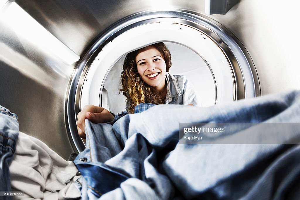 Smiling blonde beauty loads her washing machine: seens from inside