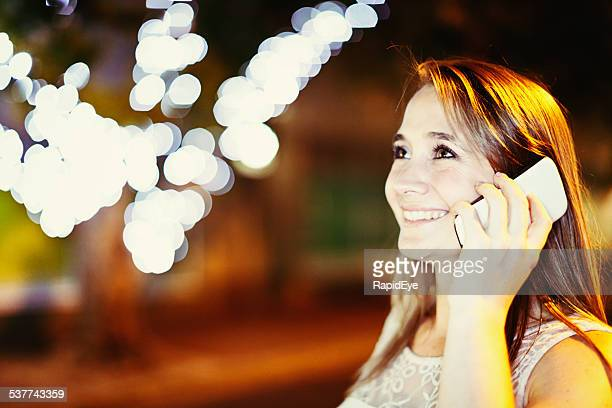 Smiling blonde, brown-eyed beauty chatting on smartphone under twinkling lights
