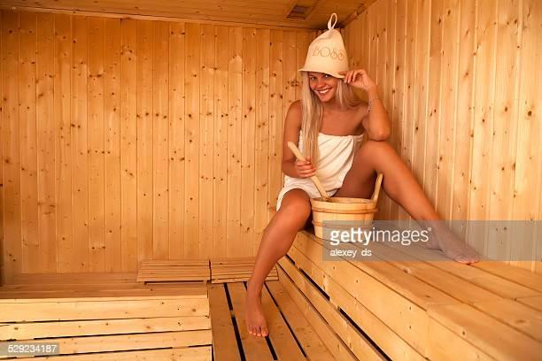 Smiling blonde in felt hat sits on sauna bench