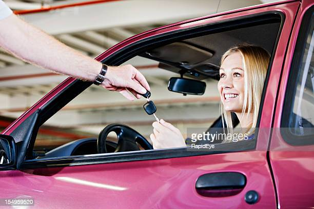 Smiling blonde is handed the keys to her new car