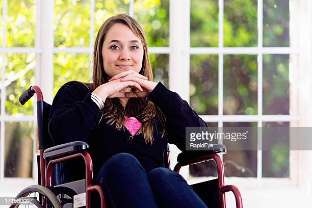 Smiling blonde woman in wheelchair, head propped on her hands