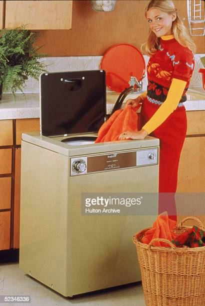 A smiling blonde woman removes a towel from a washing machine in a kitchen 1970s